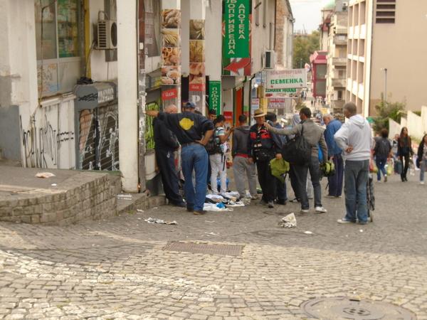 Уличная сценка в центре Белграда- сирийские беженцы продают детское питание и ООНовские рюкзаки местным торговцам на рынке.