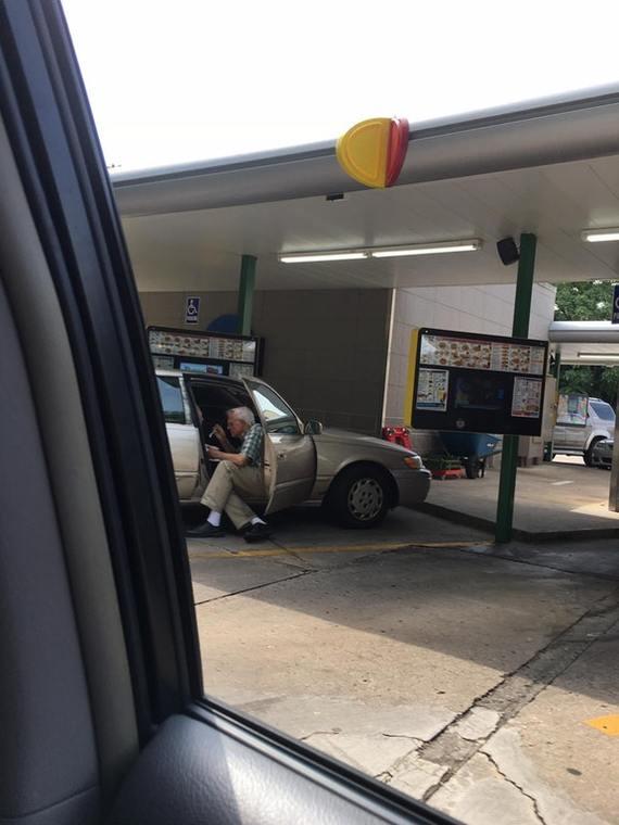Дедушка кормит мороженым свою жену, сидя за пределами авто