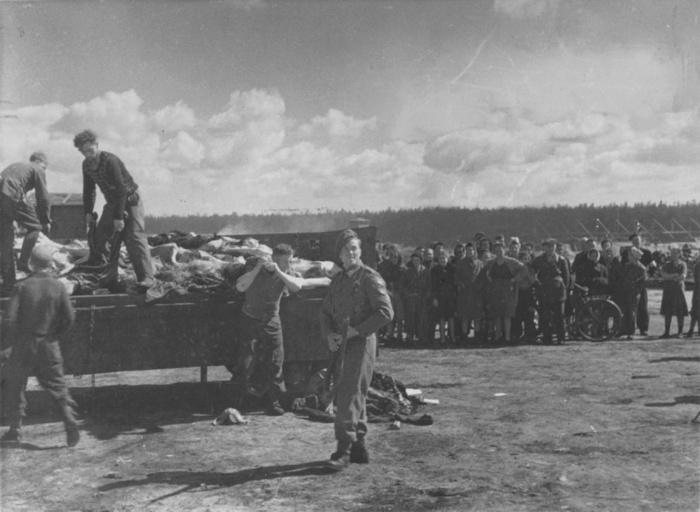 Охранники СС концлагеря Берген-Бельзен выгружают трупы узников из грузовика под конвоем британских солдат