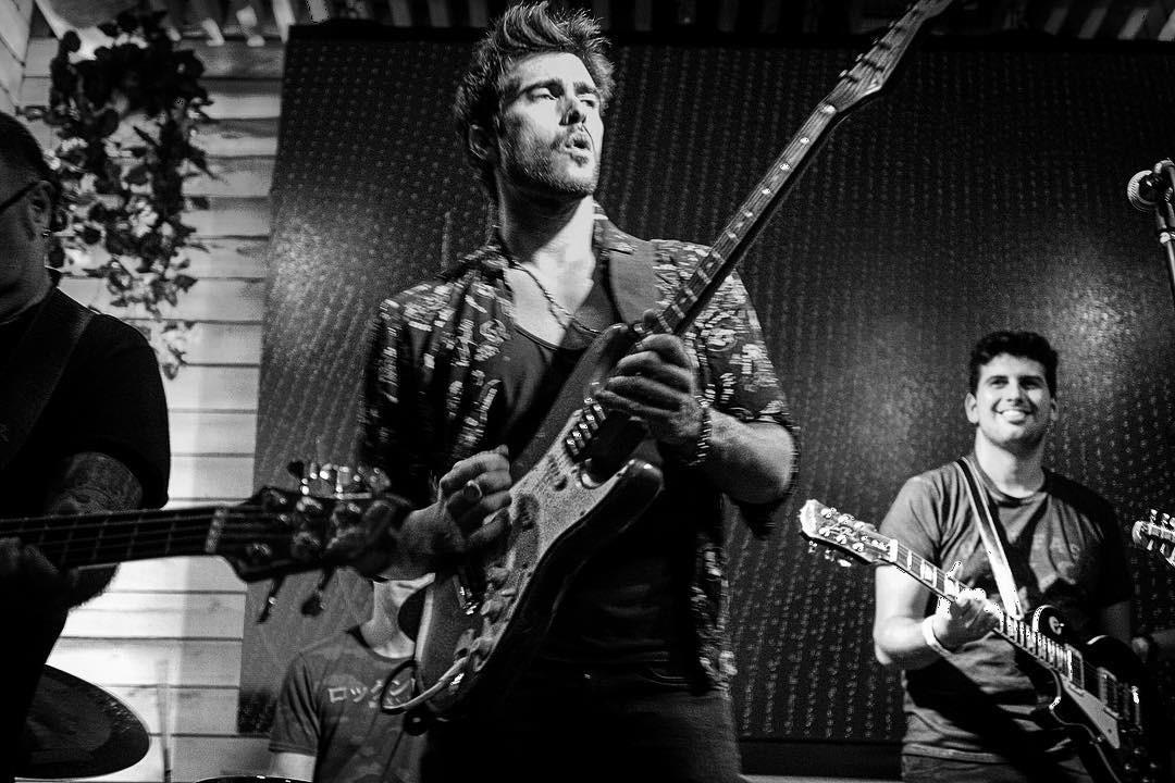 Гитарист музыкант играет на гитаре на сцене